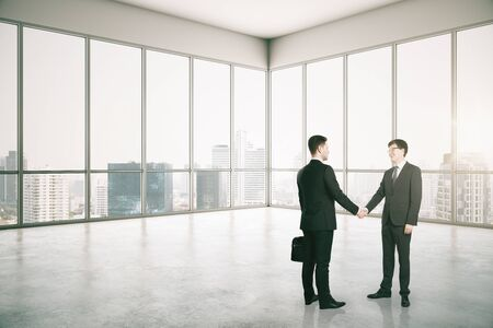 Side view of businessmen shaking hands in modern office interior with city view. Teamwork and success concept.