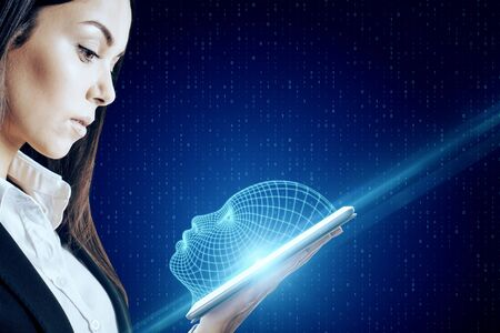 Attractive caucasian businesswoman holding tablet with glowing head outline on dark background. AI and technology concept