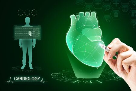 Hand pointing at creative glowing green digital heart futuristic interface hologram on dark background. Medicine, cardiology and future concept.