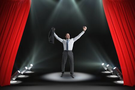 Happy businessman on abstract modern stage with spot light and red curtains. Success, leadership and star concept. Фото со стока