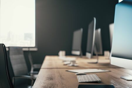 Minimalistic blurry dark coworking office interior with equipment and coffee cup on desktop, other pieces of furniture and daylight. 3D Rendering
