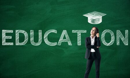 Woman with creative educational sketch on chalkboard wall background with graduation cap. Knowledge and education concept