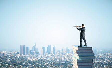 Side view of young businessman standing on books and using telescope to look into the distance on blue sky and city background. Research, education and vision concept