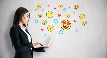 Portrait of attractive young businesswoman using laptop with emotive smileys on subtle concrete background. Communication and emotion concept Фото со стока