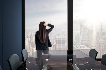 Businesswoman standing in modern meeting room interior with New York city view and daylight. Workplace concept