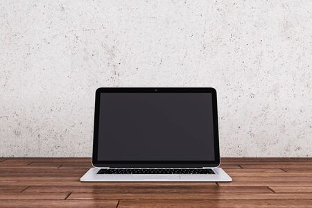 Empty laptop computer display on wooden desktop and black wall background. Online advertisement concept. Mock up, 3D Rendering Stock Photo