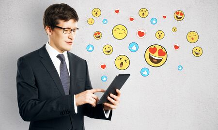 Portrait of attractive young businessman using tablet with emotive smileys on subtle background. Communication and emotion concept Фото со стока