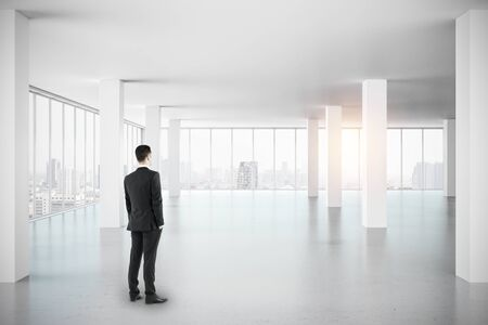 Businessman looking out of window in empty white office interior with city view and daylight. Research concept.