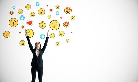 Portrait of happy young businesswoman with emotive smileys on subtle white background. Communication and emotion concept