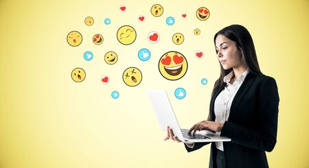 Portrait of attractive young businesswoman using laptop with emotive smileys on yellow blue background. Communication and emotion concept Фото со стока
