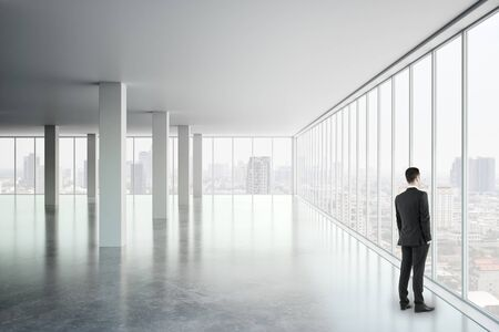 Businessman looking out of window in modern white office interior with city view and daylight. Research concept. Фото со стока