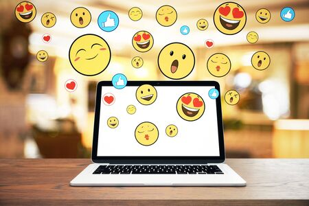 Close up of laptop with emotive smileys on wooden desktop and blurry interior background. Communication concept Stock Photo