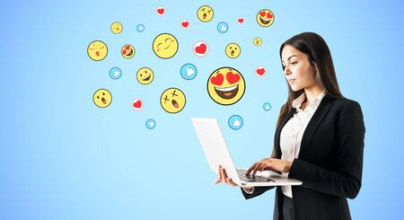 Portrait of attractive young businesswoman using laptop with emotive smileys on subtle blue background. Communication and emotion concept