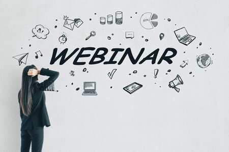 Stressed young businesswoman looking at webinar sketch on white wall background with icons. Internet and education concept Фото со стока