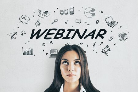 Portrait of attractive thoughtful young businesswoman on concrete wall background with webinar sketch