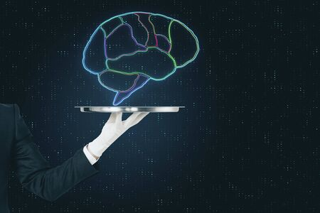 Digital human brain divided by lobes on metal tray in the hands of a waiter at abstract background.