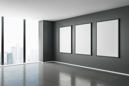 Blank white mock up posters on dark wall in modern empty room with concrete floor and city view. 3D Rendering