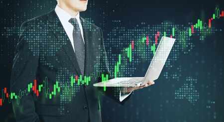 Businessman traider with laptop and digital screen with forex graphs and pixel world map.Double exposure. Stock Photo