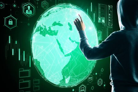 Business security concept with hacker back touching digital screen with earth globe and media icons.