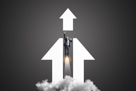 Business solution and success concept with businessman taking off in the direction of white arrow. Фото со стока