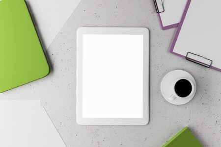 Blank white digital tablet screen on the table around coffee mug, papers and notebook, mock up. 3D Rendering Stock Photo