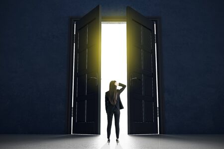 Decision making concept with businesswoman standing in front of doors in abstract bright space.