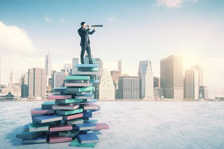 Career growth and personality development concept with businessman on book mountain looking through a telescope.