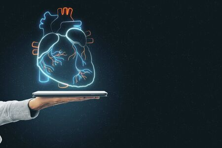 Heart online diagnostics concept with human hand with digital tablet and hologram heart pattern above.