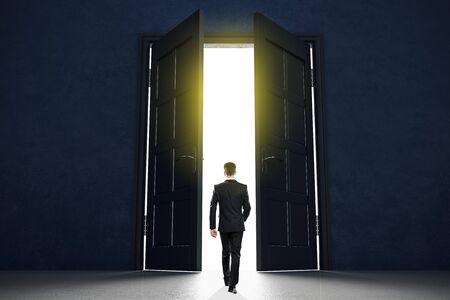 Neues Konzept für den Anfang des Lebens mit Geschäftsmann, der offene schwarze Türen in abstraktem hellem Raum betritt. Standard-Bild
