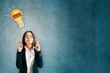 Portrait of attractive young european businesswoman with crossed fingers and lamp sketch on concrete wall background with copyspace. Idea and hope concept