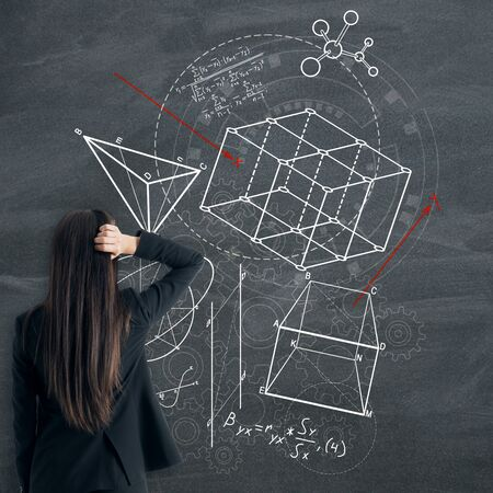 Back view of worried businesswoman looking at creative geometric figures sketch on blackboard background. Geometry, science and education concept Stockfoto