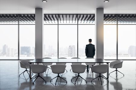 Back view of businessman standing in modern meeting room interior with panoramic city view, reflections on concrete floor and daylight. Research concept. 3D Rendering