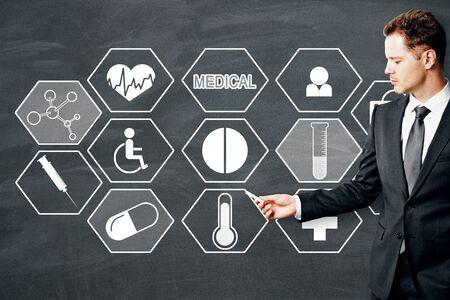 Businessman drawing creative medical sketch on chalkboard background. Medicine and innovation concept