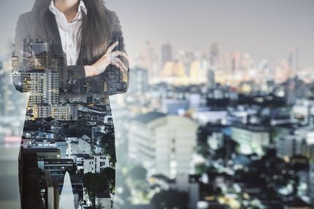 Unrecognizable businesswoman standing on night city background. Career and success concept. Multiexposure 写真素材