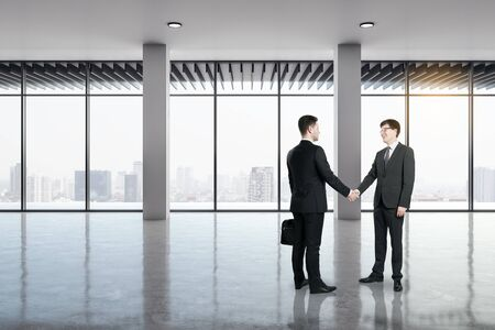 Businessmen shaking hands in modern office interior with city view and daylight. Teamwork and success concept.