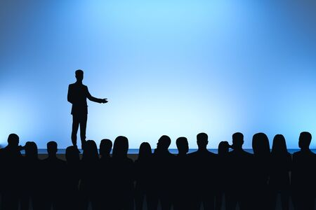Man giving speech in front of backlit audience on light blue background. Speaker and leadership concept