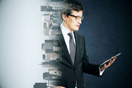 Portrait of attractive young european businessman using digital pad on abstract city background. Success, technology and communication concept. Multiexposure Banco de Imagens