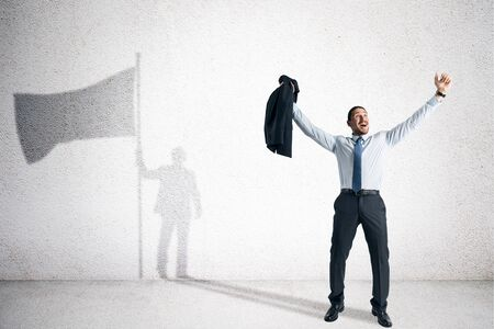 Happy young european businessman with flag shadow in white interior. Leadership and development concept.