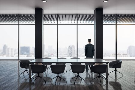 Back view of businessman standing in modern conference room interior with panoramic city view, reflections on wooden floor and daylight. Research concept.