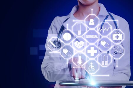 Medicine and tech concept. Doctor hand holding tablet with creative glowing blue medical interface on dark background. Double exposure Reklamní fotografie
