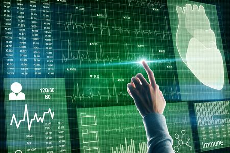 Medicine and technology concept. Hand using creative glowing green medical cardiology interface on dark background. 版權商用圖片