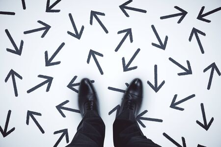 Vista superior de los pies del empresario con flechas sobre fondo gris.