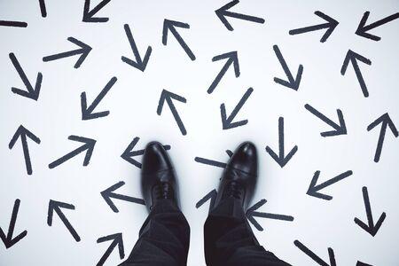 Vue de dessus des pieds d'homme d'affaires avec des flèches sur fond gris.
