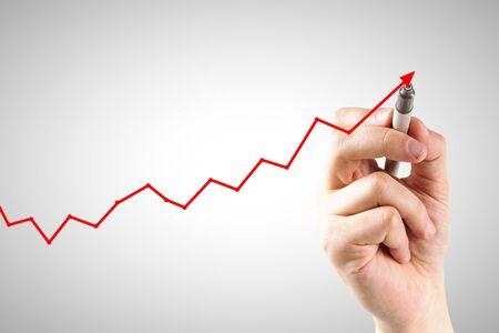 Hand die opwaartse rode pijl trekt op subtiele lichte achtergrond. Economische groei en recessie concept Stockfoto