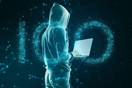 Hacker using laptop with creative glowing polygonal ICO hologram on dark background. Initial coin offering and malware concept. Double exposure