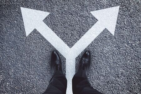 Top view of businessman feet with arrows on concrete background. Different direction and way concept