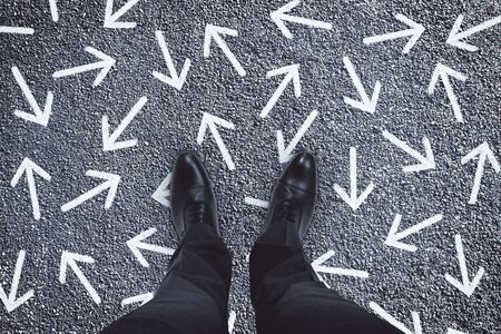 Top view of businessman feet with arrows on concrete background.