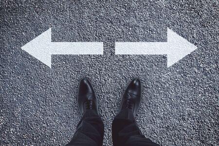 Draufsicht der Geschäftsmannfüße mit Pfeilen auf konkretem Hintergrund. Unterschiedliches Richtungs- und Chancenkonzept