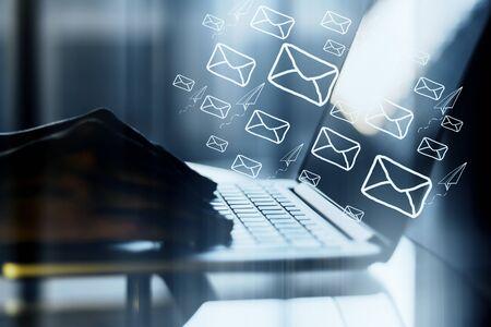 Vista lateral de las manos usando la computadora portátil en el escritorio con correos electrónicos digitales sobre fondo borroso. Concepto de comunicación y red de correo electrónico. Exposición doble