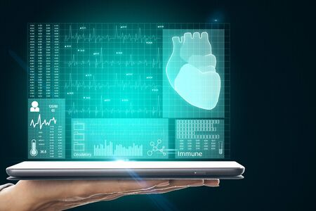 Hand holding tablet with abstract medical cardiology interface on dark blurry background. Medicine and science concept